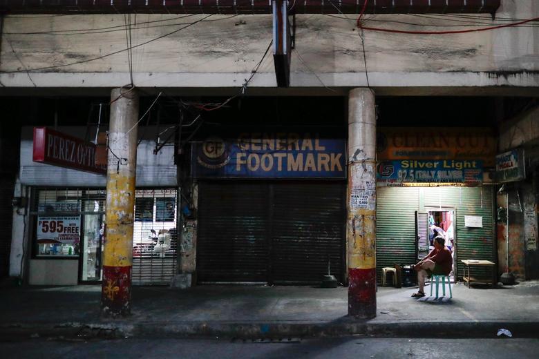 Người đàn ông ngồi đợi đóng cửa cửa hàng vào tối 24/3 tại Manila, Philippines. Từ giữa tháng 3, Manila đã bị phong toả khi số ca nhiễm SARS-CoV-2 có dấu hiệu tăng nhanh.
