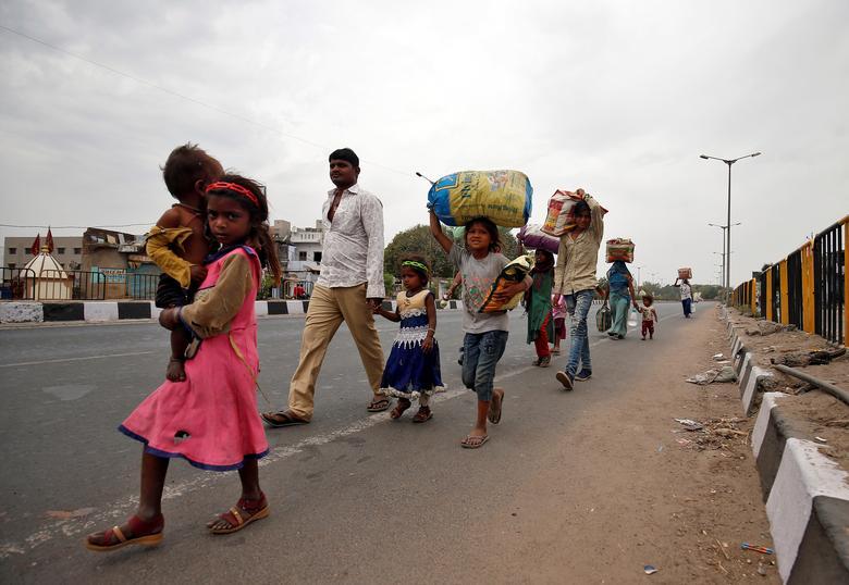 Công nhân nhập cư ở Ahmedabad đi bộ cùng các con để tìm phương tiện di chuyển về làng quê vào ngày 25/3.