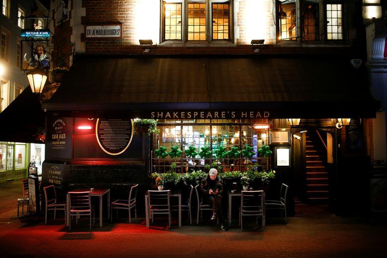 Trước khi đóng cửa hoàn toàn, chính quyền Anh vẫn cho phép một số hàng quán mở cửa nhưng không ai đến do lo ngại ảnh hưởng dịch bệnh. Trong ảnh là một người đàn ông ngồi đơn độc trước một quán ở London vào ngày 17/3.