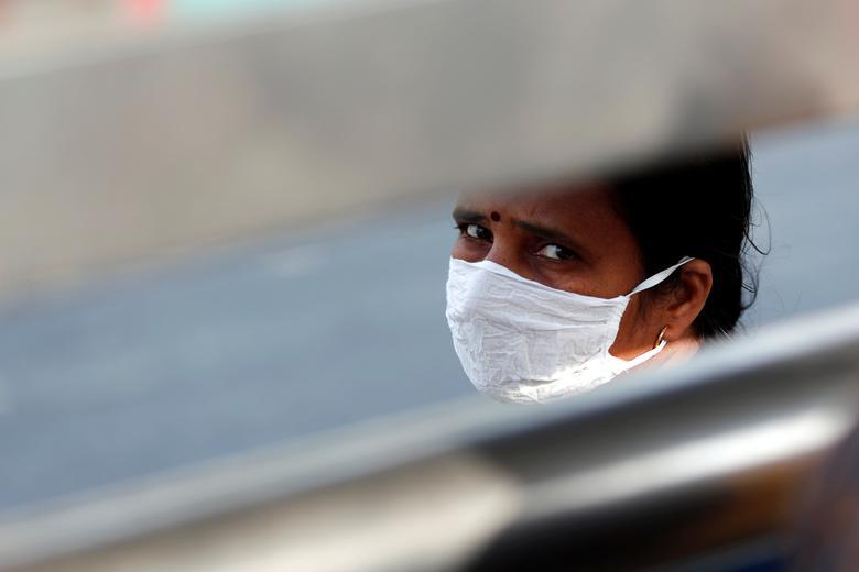 Một người phụ nữ đang chờ xe buýt để trở về quê vào ngày 23/3 tại New Delhi.