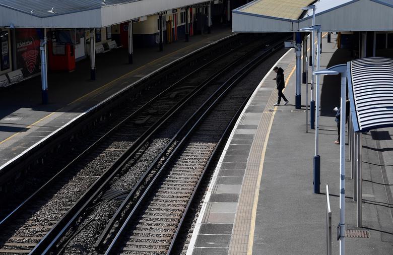 Một hành khách chờ đợi xe lửa ở ga Richmond, London vào ngày 24/3.