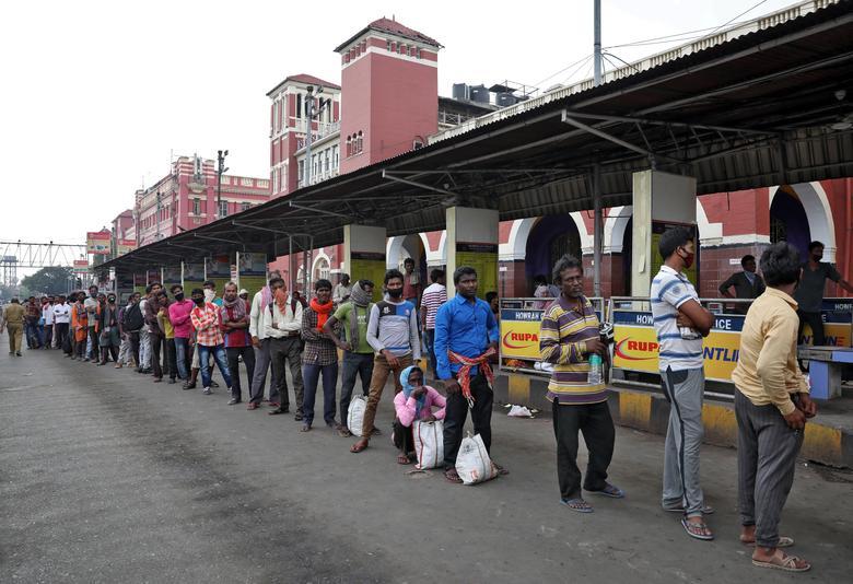 Công nhân nhập cư chờ xếp hàng để nhận thức ăn miễn phí bên ngoài nhà ga Howrah ở Kolkata vào ngày 25/3.
