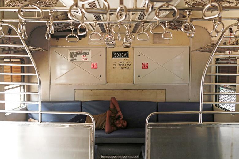 Một nhân viên tàu hoả nằm trong khoang tàu trống rỗng khi lệnh cấm phương tiện vận chuyển công cộng được ban bố