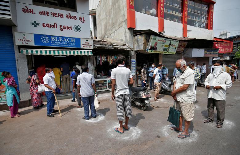Người dân xếp hàng mua thuốc phải đứng trong những ô tròn được kẻ bằng phấn để giữ khoảng cách an toàn vào ngày 26/3 tại Ahmedabad.
