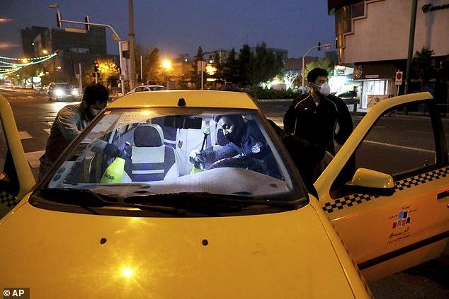 Lực lượng vệ binh cách mạng Iran phối hợp khử trùng một chiếc taxi ở Tehran.
