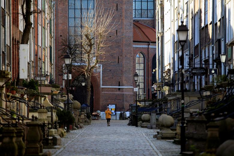 Main Town ở Gdansk, Ba Lan là nơi thường xuyên đông đúc nhưng từ khi dịch bệnh bùng phát đã trở nên vắng lặng hẳn. Một người phụ nữ đi qua con phố vào ngày 23/3 không có một bóng người.