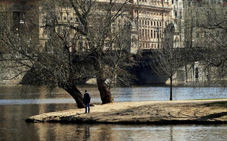 Người đàn ông đeo khẩu trang để ngắm nhìn công viên ở Prague, cộng hoà Séc vào ngày 23/3. Khung cảnh xung quanh trông đìu hiu vì không có con người.
