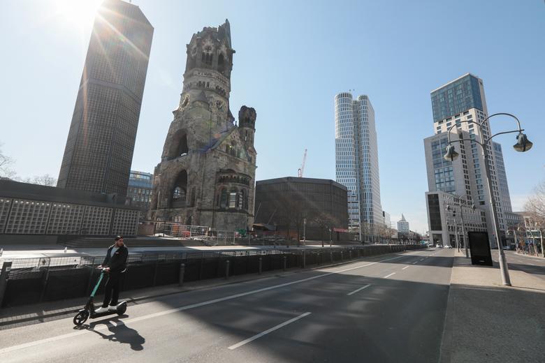 Một người lái xe điện di chuyển trên đường phố vắng lặng ở Berlin, Đức vào ngày 25/3.