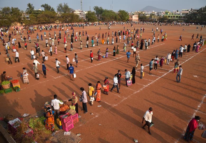 Người dân xếp hàng mua rau phải đứng trong những ô kẻ sẵn giữ khoảng cách an toàn một sân vận động biến thành một khu chợ tạm ở Vijayawada ở bang miền nam Andhra Pradesh, Ấn Độ