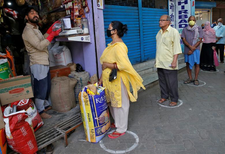 Tại một cửa hàng tạp hoá nhỏ ở Kolkata, người mua hàng cũng phải đứng cách xa nhau để giữ khoảng cách an toàn. Bức ảnh được chụp ngày 26/3.