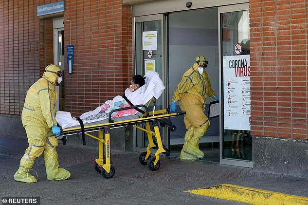 Nhân viên cứu thương trong trang bị bảo hộ đầy đủ đưa bệnh nhân đến Bệnh viện Severo Ochoa.