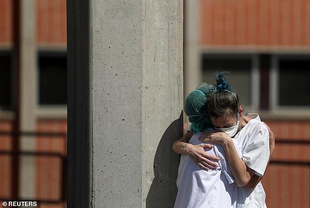 Nhân viên y tế an ủi nhau bên ngoài phòng cấp cứu tại Bệnh viện Severo Ochoa.