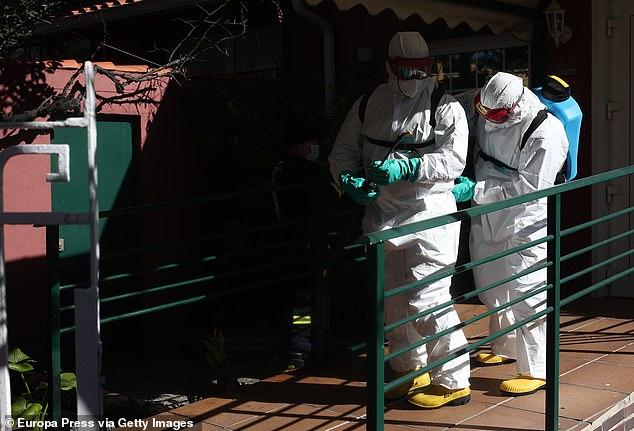 Các nhân viên quân đội chuẩn bị sẵn sàng để khử trùng một viện dưỡng lão.