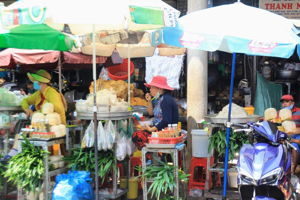 Tiểu thương còn ăn uống, cười nói với nhau như thói quen hằng ngày tại chợ.