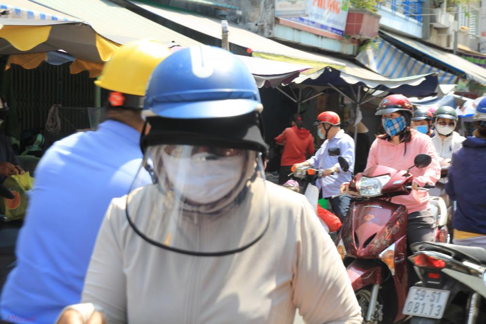 Ngược lại với các tiểu thương, đa số người đi chợ khá kỹ càng trong ngày dịch. Ngoài khẩu trang, nhiều người còn dùng cả mũ chống dịch, bao tay,...