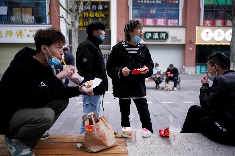 Một số thanh thiếu niên đang ăn uống trước một cửa hàng McDonald tại Vũ Hán vào ngày 30/3. Hôm 23/1, chính quyền đã quyết định phong toả Vũ Hán (nơi khởi nguồn của dịch bệnh viêm phổi) để ngăn chặn dịch bệnh lây lan. Cuộc sống của 11 triệu dân nơi đây gần như bị đảo lộn.