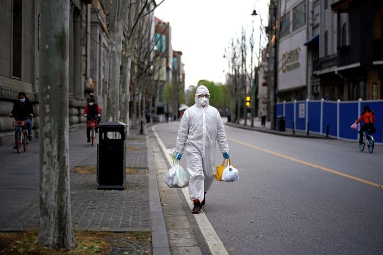 Một người đàn ông mặc đồ bảo hộ, đeo khẩu trang cẩn thận khi ra ngoài mua sắm vào ngày 30/3.