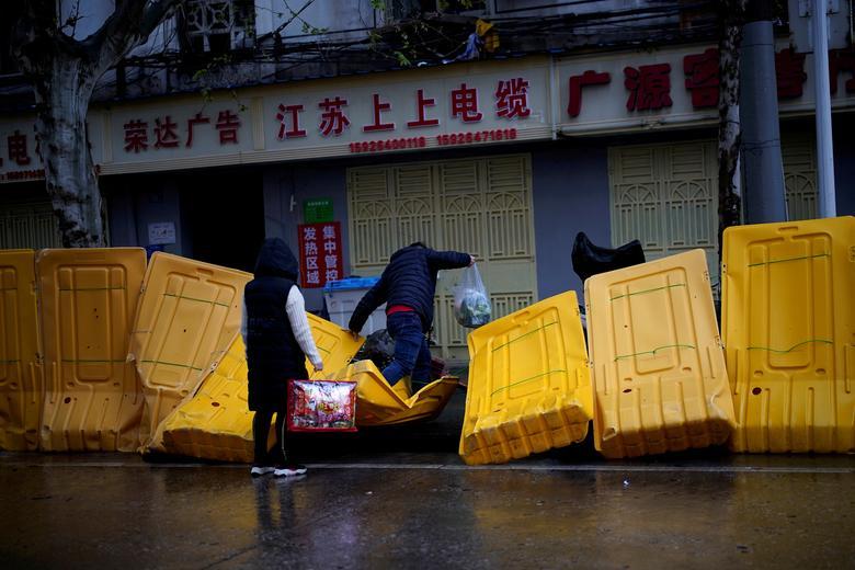 Người dân bước qua một hàng rào cách ly đã bị sập vào ngày 29/3. Nnững ngày Vũ Hán bị phong toả, các gia đình đều bị giới hạn việc di chuyển, taxi, phương tiện giao thông công cộng ngừng hoạt động... Cuộc sống của người dân chỉ gói gọn trong căn nhà của họ.
