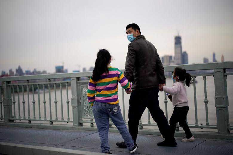 Người cha dẫn theo 2 cô con gái tản bộ trên một cây cầu ở Vũ Hán vào sáng 28/3. Khung cảnh xung quanh trông vẫn khá vắng lặng, đìu hiu.