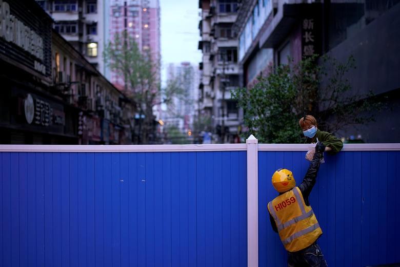 Một nhân viên giao hàng cho khách thông qua bức tường chắn ngăn chặn lối ra vào tạo một khu dân cư ở Vũ Hán vào ngày 28/3.