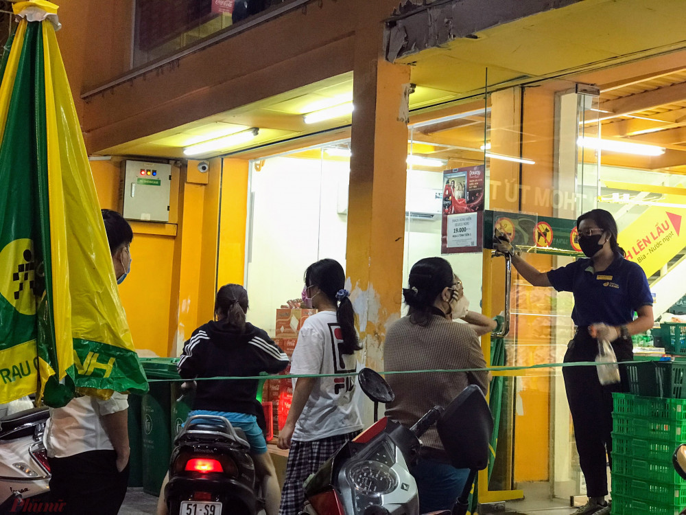 Một cửa hàng bách hoá trên đường Vũ Tùng (quận Bình Thạnh, TPHCM) khách hàng phải xếp hàng mỗi lần nhân viên chỉ cho vào 4-5 khách, cửa hàng chốt chặn xác khuẩn cho khách trước khi mua hàng.