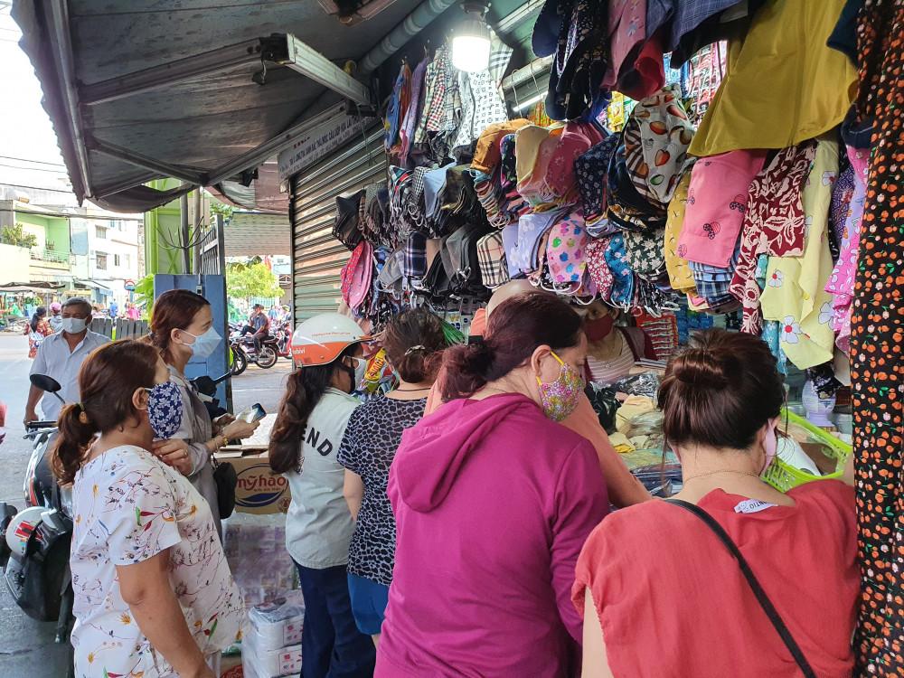 Ở một góc chợ khác, các cô các chị đang tranh thủ mua khẩu trang
