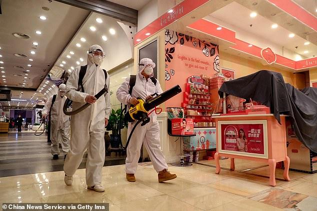 Nhân viên y tế mặc đồ bảo hộ thực hiện công việc khử trùng tại Trung tâm mua sắm Wushang Plaza ở Vũ Hán.