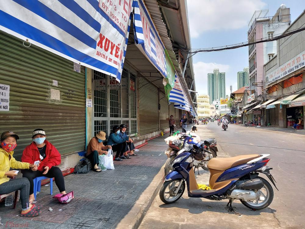 Các cửa hàng ở chợ Kim Biên đóng cửa, nhiều người tận dụng mái hiên trong chợ làm nơi nghỉ mát giữa trưa.
