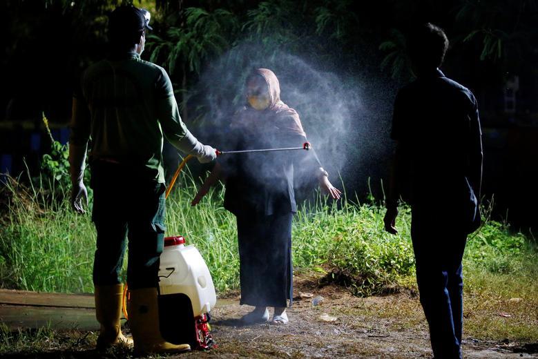 Nhân viên xịt khử trùng một người thân của bệnh nhân mắc COVID-19 tại thủ đọ Jakarta, Indonesia vào ngày 31/3. Bên cạnh xịt khử trùng, Jakarta cũng xây bồn rửa tay, bố trí buồng khử trùng trên khắp thành phố để góp phần đẩy lùi dịch bệnh.