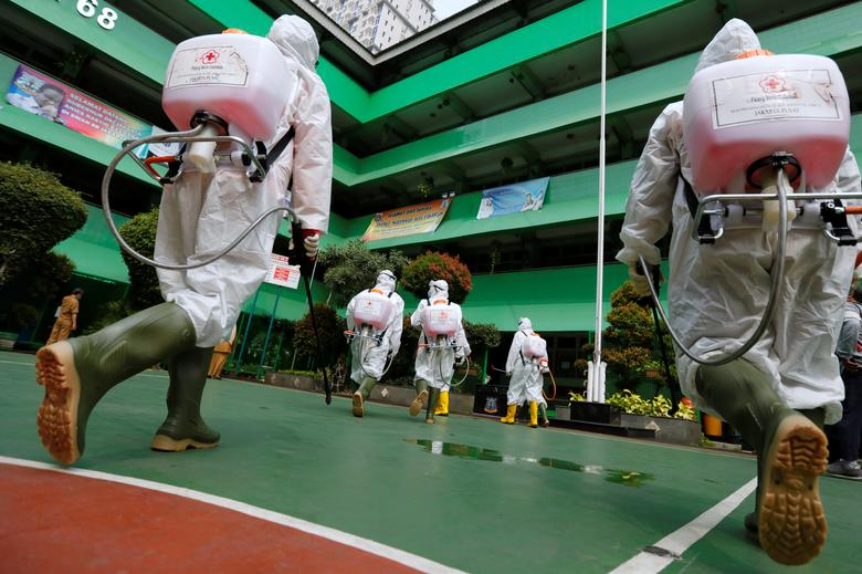 Nhóm tình nguyện viên của Hội chữ thập đỏ Indonesia tiến vào bên trong một trường học để phun thuốc khử trùng. Ngày 24/3, chính quyền Indonesia cho biết sẽ hoãn kỳ thi p