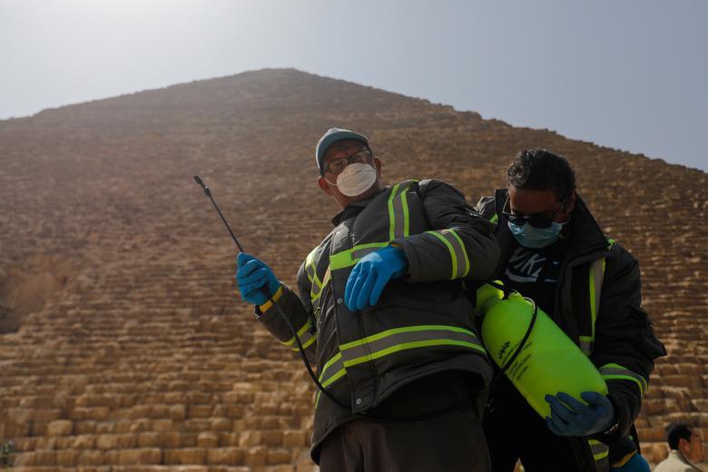 Nhân viên y tế đang chuẩn bị phung khử trùng tại khu vực bên ngoài Kim Tự Tháp ở Cairo, Ai Cập vào ngày 25/3. Đây là một trong những biện pháp của chính quyền Ai Cập để ngăn chặn dịch bệnh. Tối 30/3, tại Đại Kim Tự Tháp, chính quyền đã cho chiếu đèn led để truyền đi một số thông điệp như: