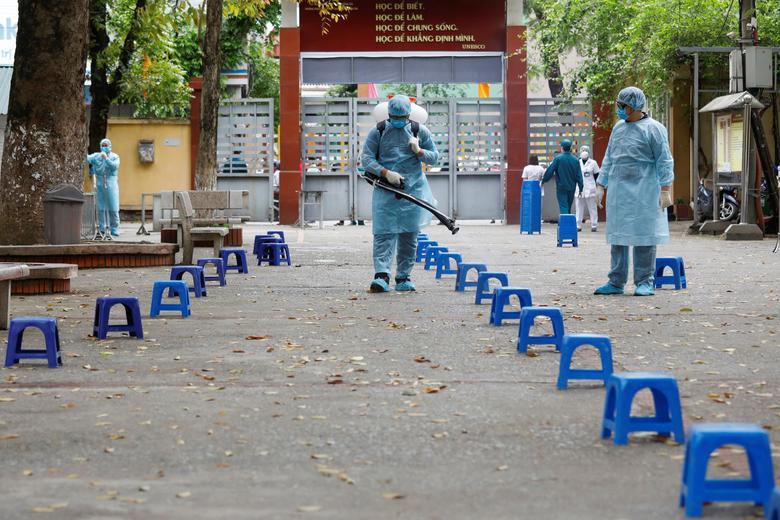 Nhân viên y tế phun thuốc khử trùng tại khu vực xét nghiệm nhanh ở thủ đô Hà Nội vào ngày 31/3 cũng được Reuters đăng tải.