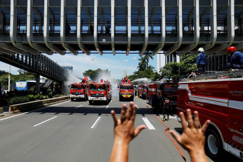 Một hàng xe cứu hoả được dùng phun thuốc khử trùng tại Jakarta, Indonesia vào ngày 31/3. Trong ảnh, người chỉ huy đang giơ tay ra hiệu lệnh dừng phun để tiếp tục đổ đầy thuốc vào bồn.