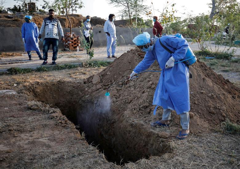 Nhân viên y tế phun khử trùng nơi chuẩn bị chôn cất người chết vì mắc COVID-19 tại Ahmedabad, Ấn Độ vào ngày 29/3.