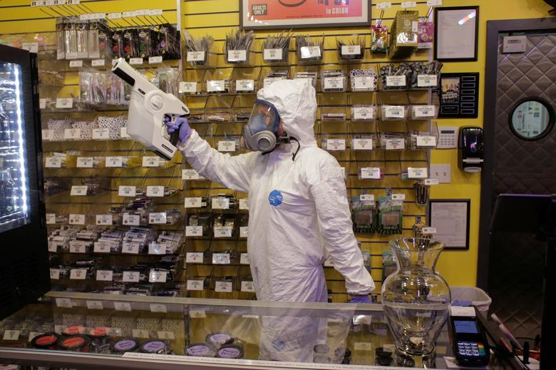 Nhân viên y tế dùng máy phun tĩnh điện để khử trùng một cửa hàng tại Seattle, Washington và ngày 30/3.