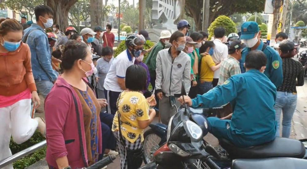 Vào sáng 31/3, những người bán vé số nghèo nhận quà từ thiện của một chủ đại lý vé số