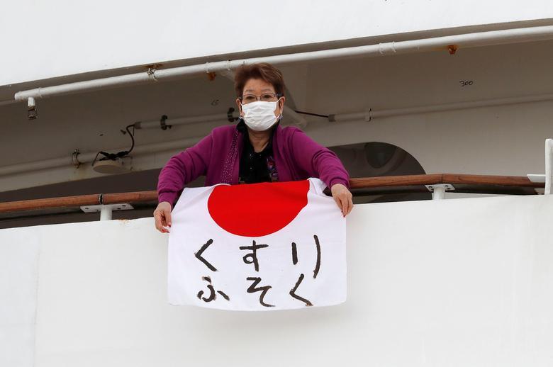 Một người phụ nữ giơ bảng ghi dòng chữ thiếu thuốc từ ban công trên tàu Diamond Princess.