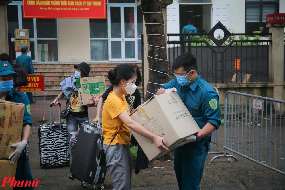 Lực lượng dân phòng, bộ đội khẩn trương hỗ trợ người dân thu dọn đồ đạc và vận chuyển lên xe buýt.