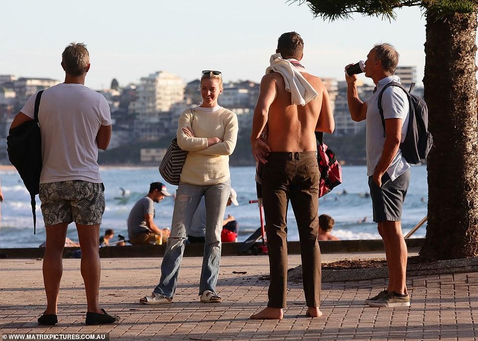 Một nhóm khách đứng nói chuyện trên bờ biển, giữ khoảng cách tối thiểu 1,5 m.