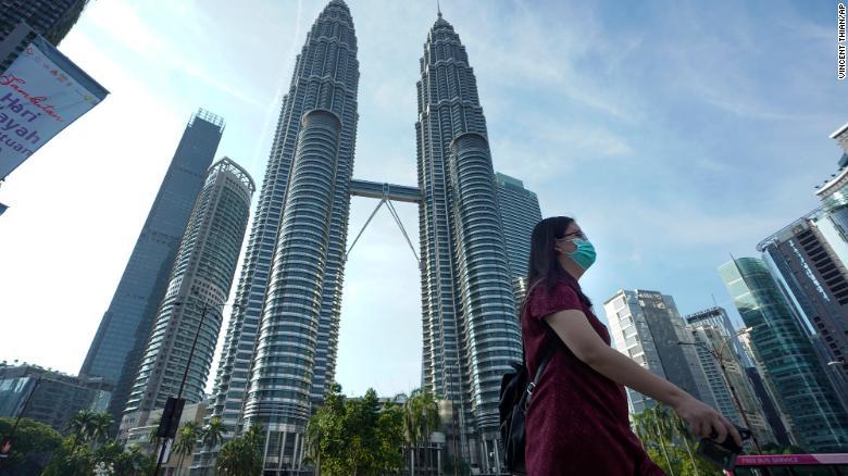 Một phụ nữ Malaysia đeo khẩu trang đi ngang tòa tháp Twin Towers ở Kuala Lumpur. Ảnh: CNN