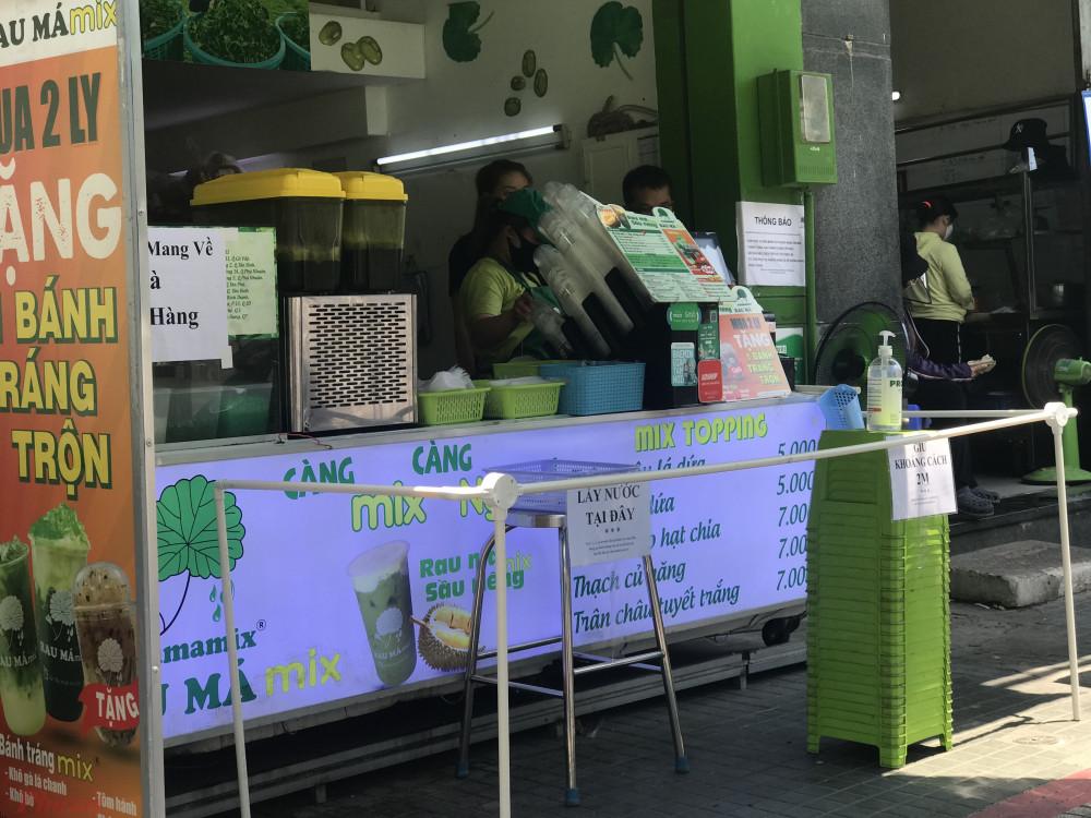 Một điểm bán nước trên đường Phan Xích Long (quận Phú Nhuận, TPHCM) ngoài thực hiện việc không cho khách uống tại chỗ, cửa hàng này còn bố trí đặt nước, thanh toán, lấy hàng ở phạm vi nhất định tránh việc tiếp xúc trược tiếp với người mua và người bán.