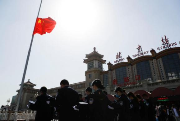 Các nhân viên nhà ga Bắc Kinh cúi đầu trước lá quốc kỳ chỉ giương một nửa cột.