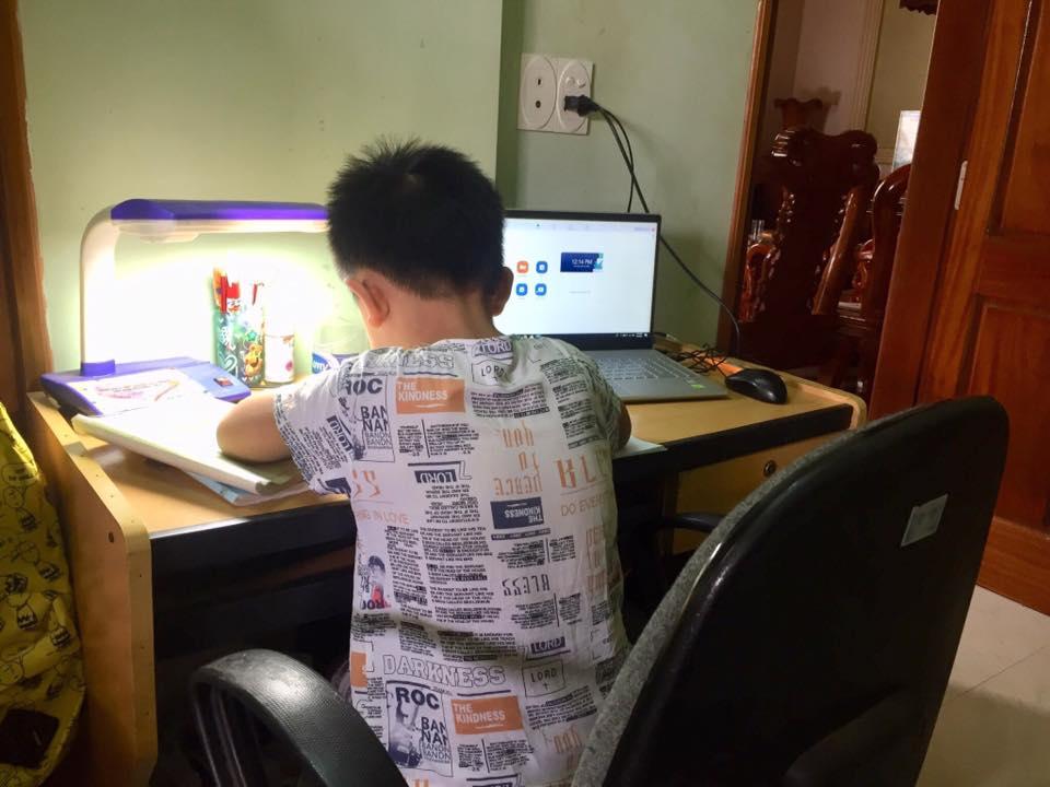Con trai út tự giác làm bài tập trong khi đợi đến giờ học trực tuyến. Ảnh NVCC