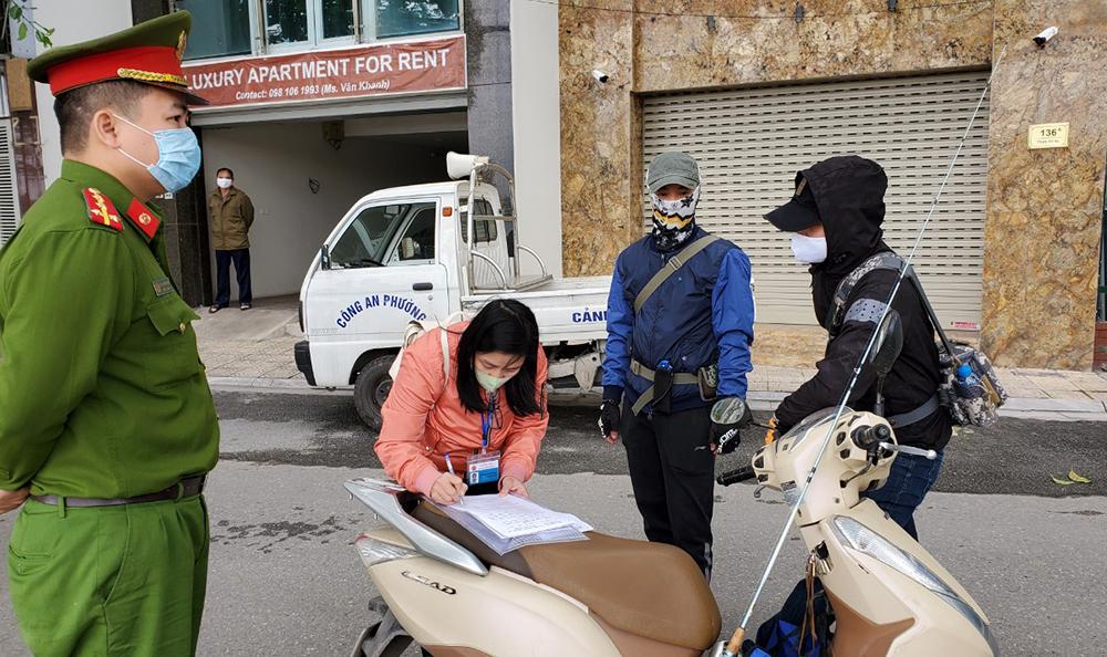 Lực lượng chức năng phường Trúc Bạch tiến hành xử phạt người ra đường không có lý do chính đáng.