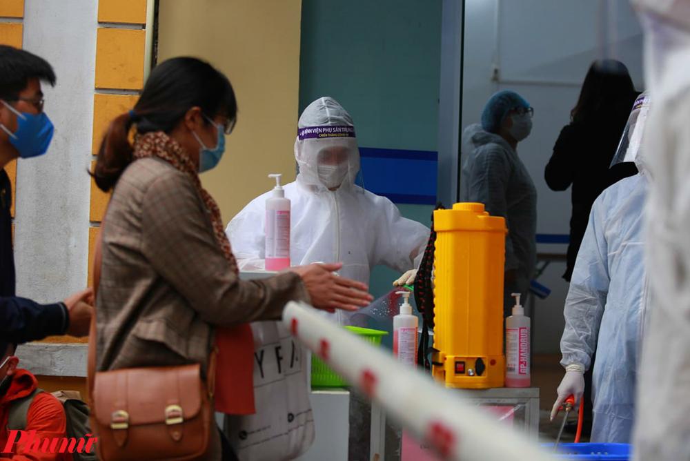 Ngoài mặt nạ, người dân còn bắt buộc phải đeo khẩu trang và sát khuẩn trước khi vào viện.