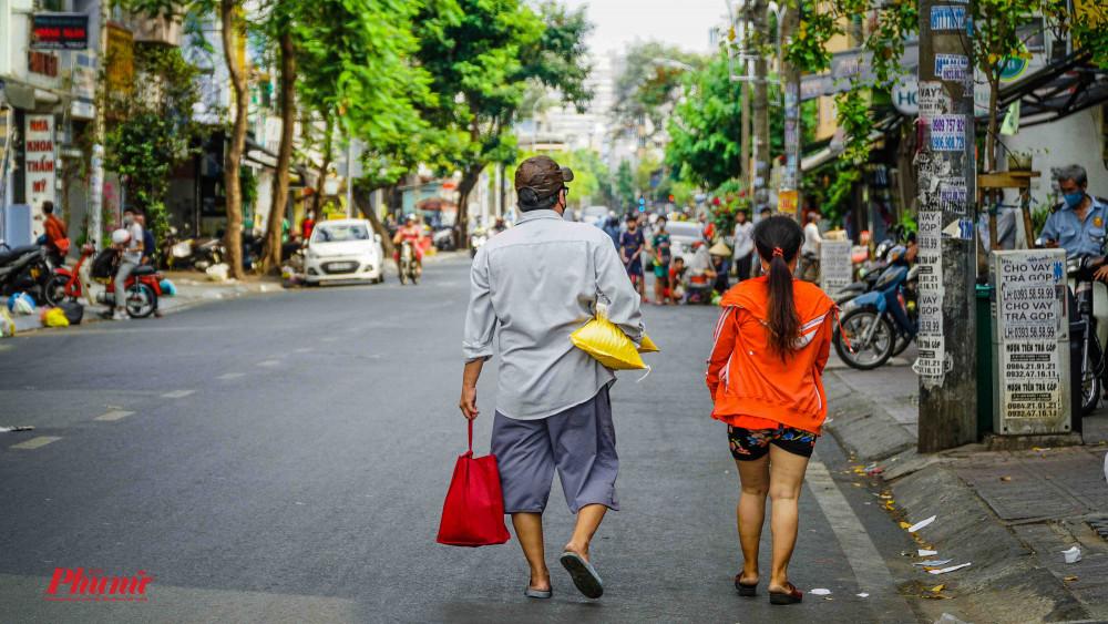 2 cha con vui vẻ ra về với bao gạo trên tay