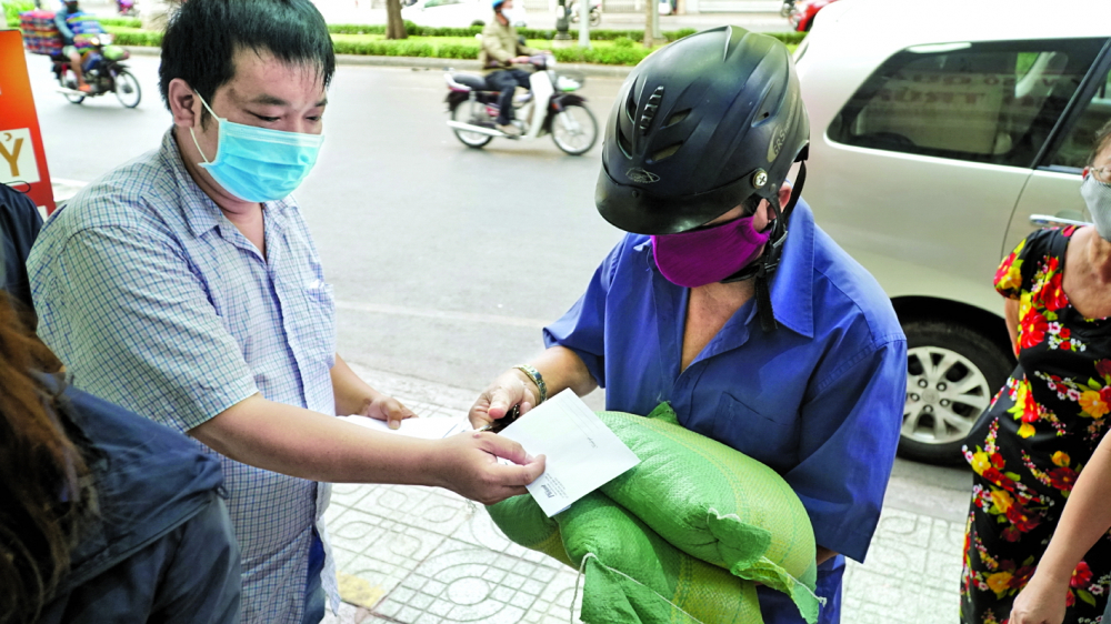 Phóng viên Báo Phụ Nữ TP.HCM trao quà cho một người bán vé số