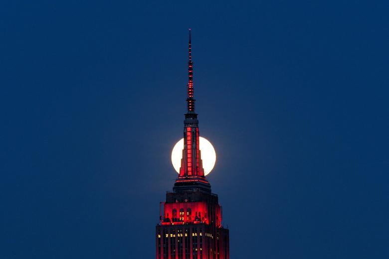 Mặt trăng như bị cắt làm đôi bởi đỉnh chóp nhọn của toà nhà cao 102 tầng Empire State Building ở New York.