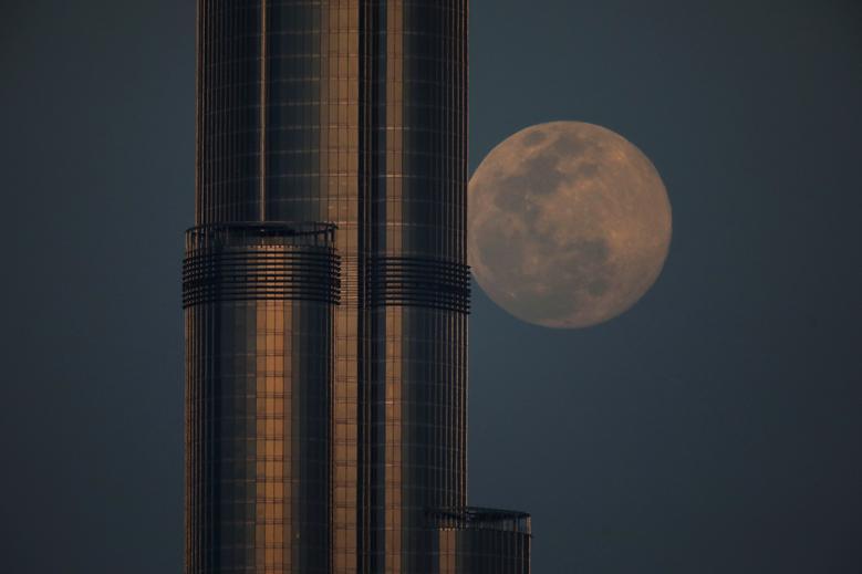 Khoảnh khắc tuyệt đẹp khi siêu trăng trông như đang tựa mình vào toà nhà chọc trời Burj Khalifa ở Dubai, các tiểu vương quốc Ả Rập Thống Nhất.