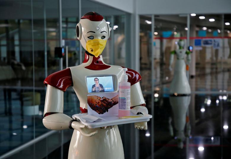 Robot được công ty Asimov Robotics của Ấn Độ sản xuất sẽ dùng tay giữ một chiếc khay có nước rửa tay, khẩu trang để đưa cho người dùng.